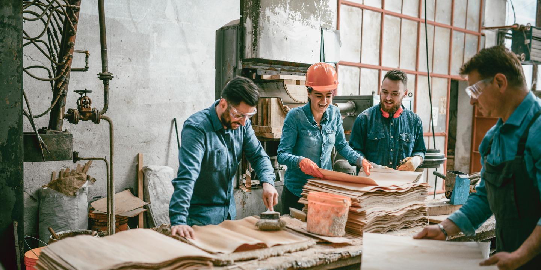 Vier Handwerker lachen zusammen in der Werkstatt