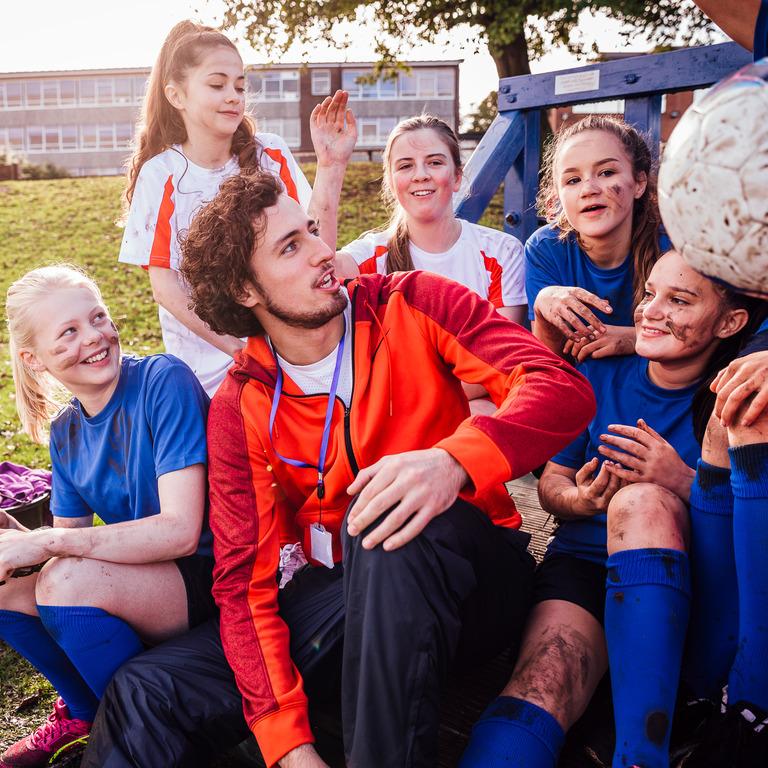 Junger Erwachsener voluntiert und trainiert eine junge Mädchenmannschaft