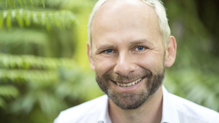 Dr. Jens Förster lächelt vor einem grünen Hintergrund in die Kamera