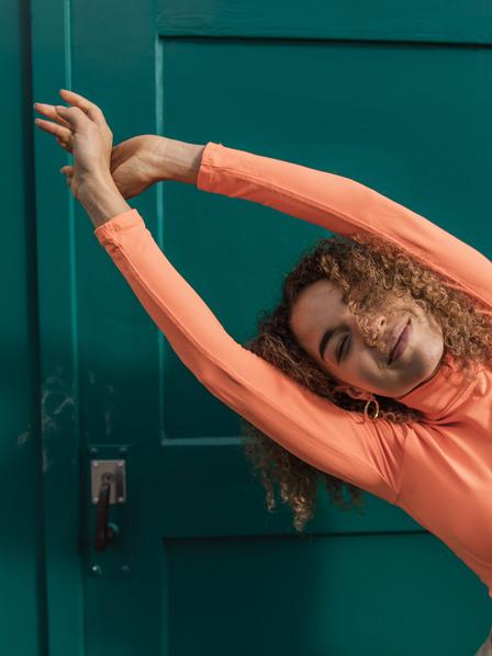 Frau in orangenem Sweatshirt dehnt ihren Oberkörper, um zu entspannen.