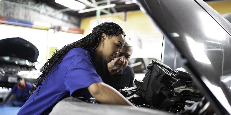 Frau mit dunkler Hautfarbe zeigt altem Mann Motor eines Autos.