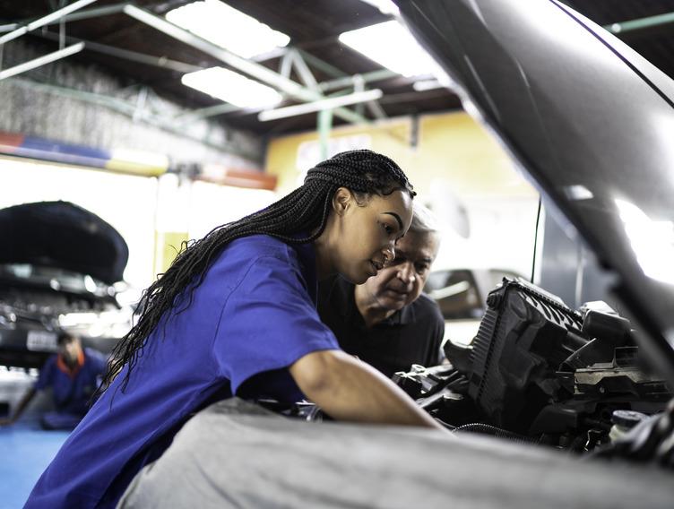 junge Kfz-Mechatronikerin arbeitet gemeinsam mit einem älteren Kollegen an einem Motor