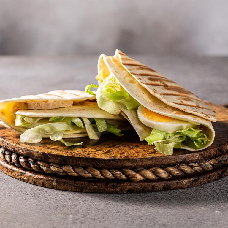 Wrap mit Ei und Salat auf einem Holzbrett serviert