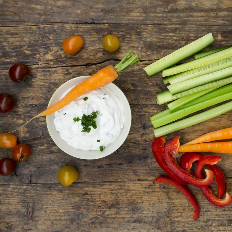 Aufsicht auf Holztisch mit Kräuterdip und geschnittenen Gemüsesticks