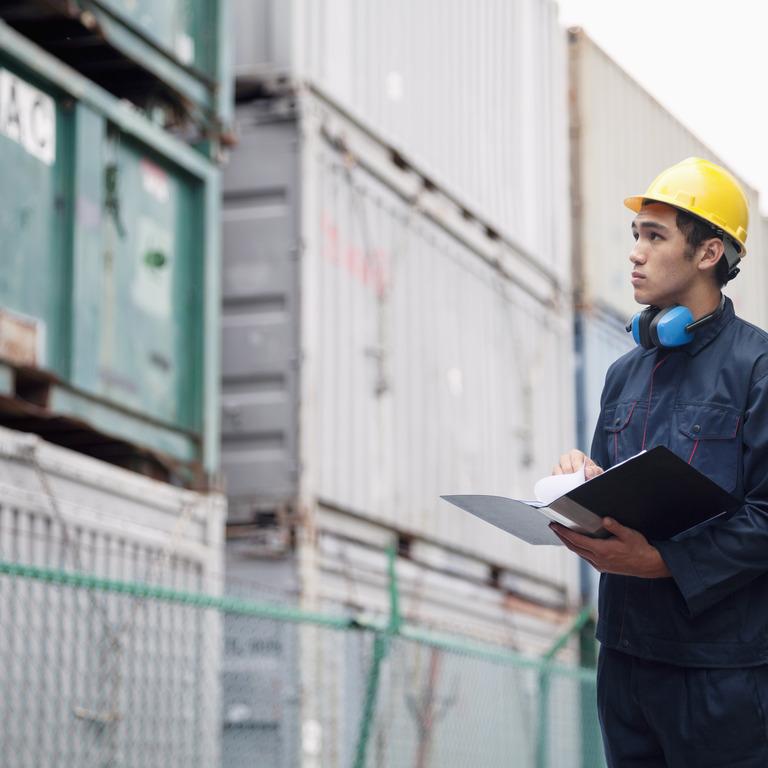 Junger Mann in Arbeitskleidung steht vor Container