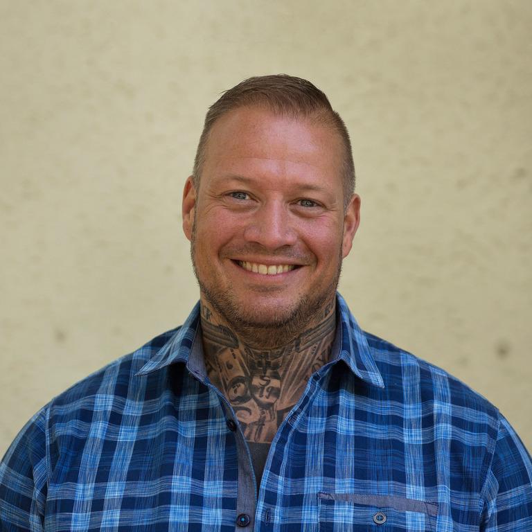 Ex-Neonazi Philip Schlaffer schaut lachend in die Kamera