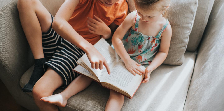 Bücher prägen unsere Sicht auf die Welt: Geschwisterpaar liest gemeinsam in einem Buch.