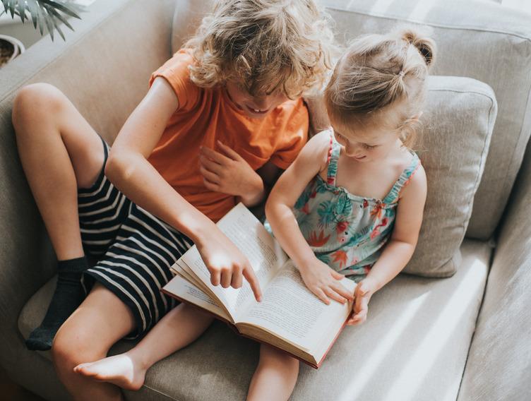 Zwei Kinder liegen mit einem Buch auf der Couch und lesen
