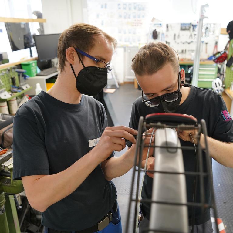 Vielfalt in der Fahrradwerkstatt: Zwei junge Erwachsene mit unterschiedlichem Hintergrund reparieren gemeinsam ein Fahrrad.