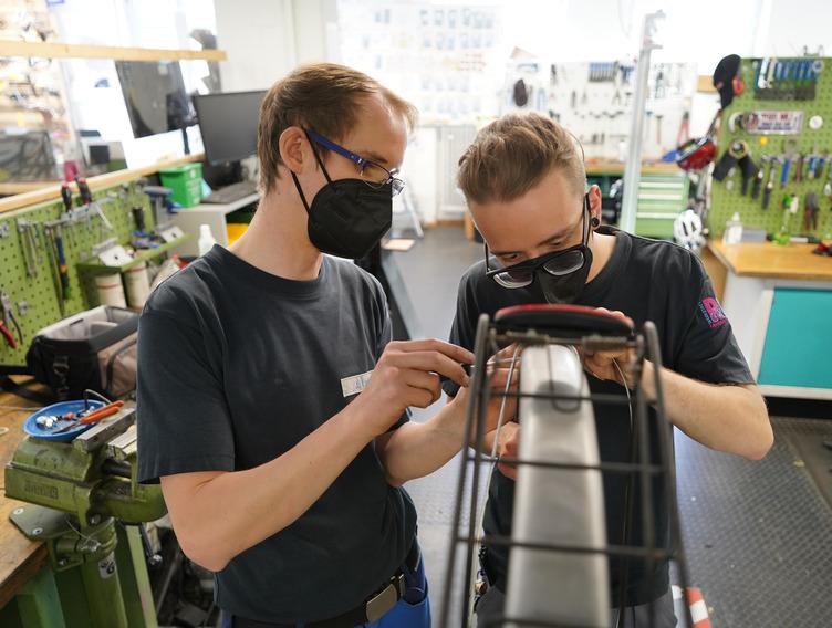 Zwei junge Männer reparieren ein Fahrrad