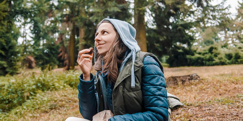 Frau snackt beim Wandern.