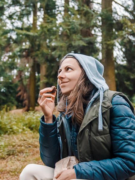 Frau macht im Wald beim Wandern eine Essenspause mit dem Proviant aus ihrem Rucksack.