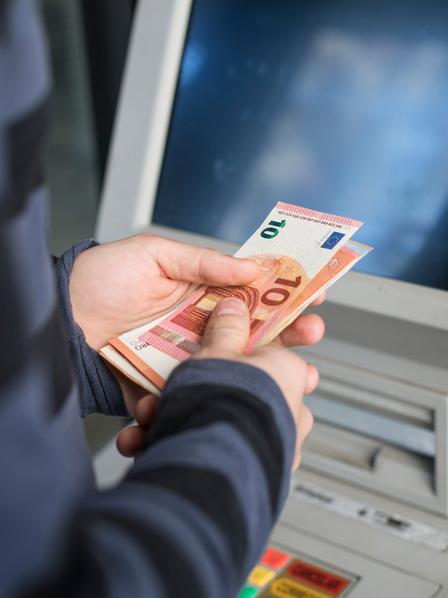 Person hebt Geld vom Automaten ab.