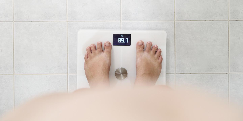 Eine Person steht auf einer Waage, die 89,1Kilogramm anzeigt – noch Normalgewicht oder schon Übergewicht?