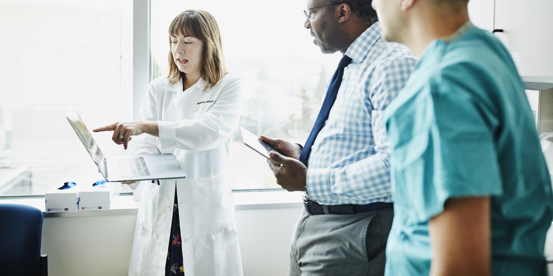 Drei Krankenhausmitarbeiter besprechen etwas am Laptop
