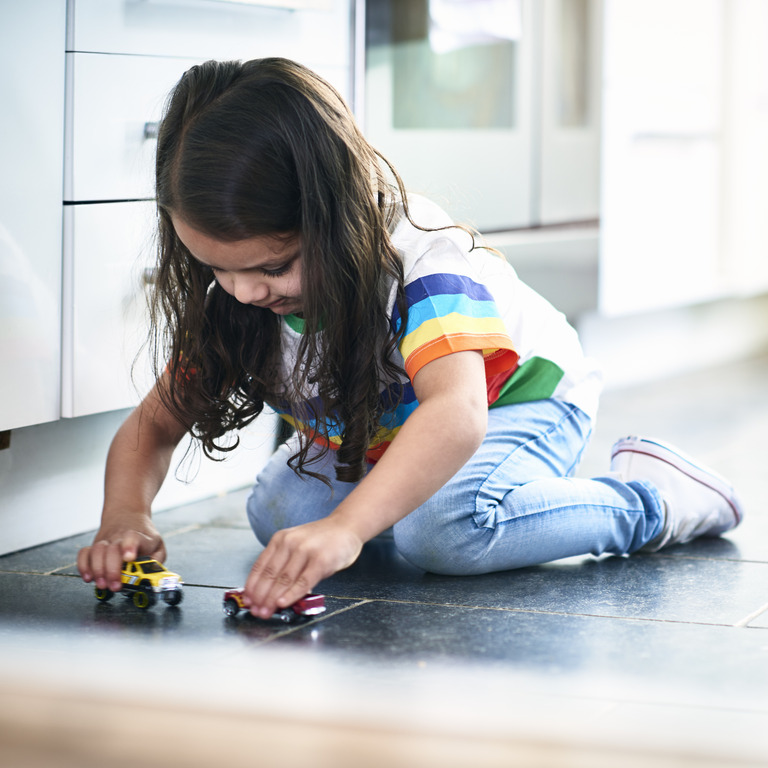 Gegen das Geschlechterklischee: kleines Mädchen spielt mit Modellautos