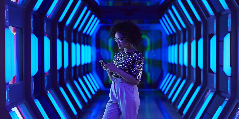 Junge Auszubildene steht in einem neonblau-beleuchtetem Gang und tippt auf ihrem Handy