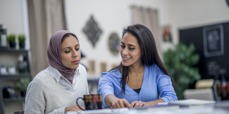 Zwei Frauen sitzen in einem Beratungsgespräch zusammen.