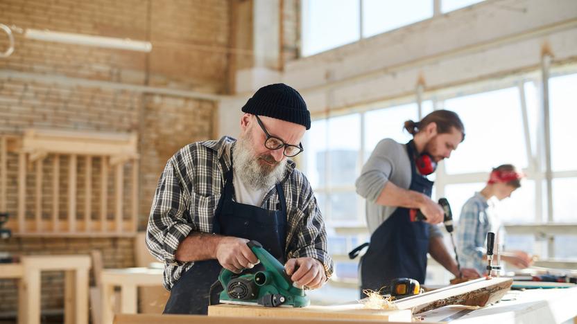 Schreiner im Seniorenalter steht gemeinsam mit jüngeren Kollegen in der Werkstatt und schleift ein Holzstück