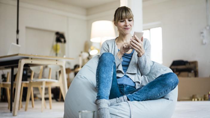 Frau sitzt auf Sitzsack und bedient ihr Smartphone.