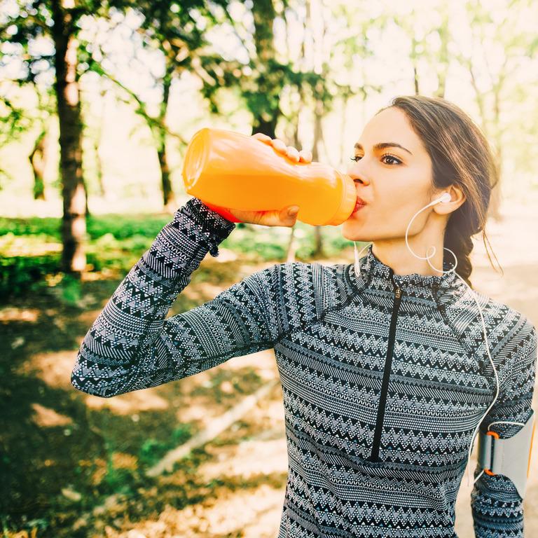 Läuferin trinkt während des Trainings aus einer Flasche