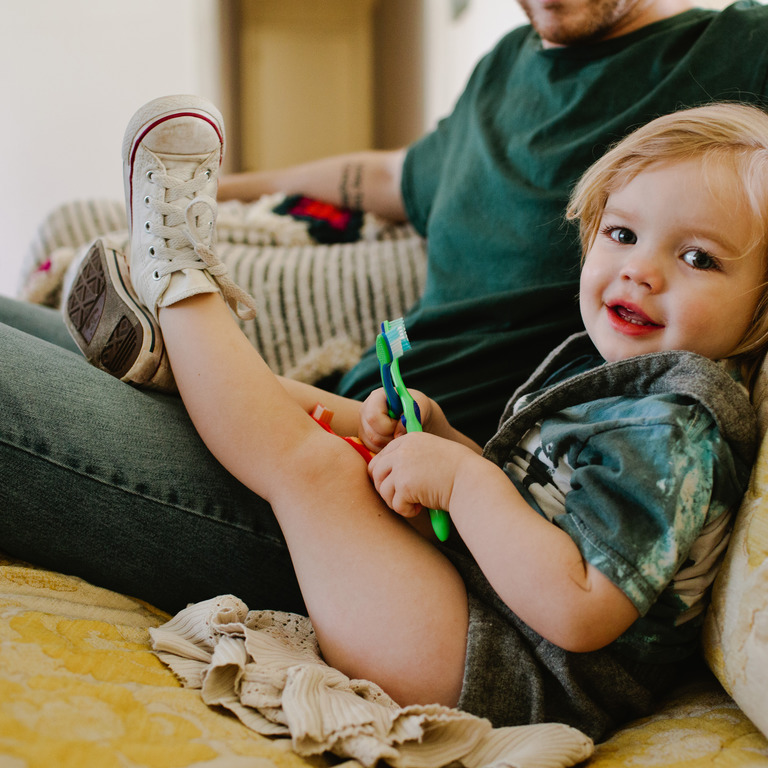 kleiner Junge sitzt auf der Couch und spielt mit verschiedenen Kinderzahnbürsten
